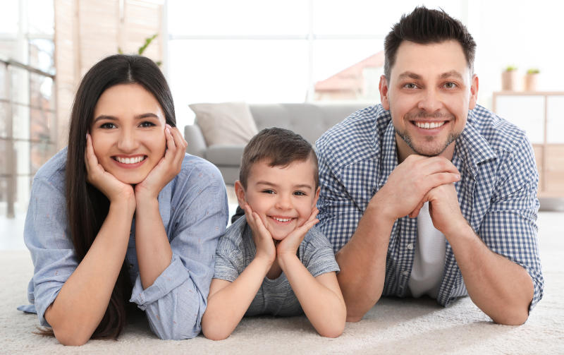 Mom, dad, and son leaning on elbows on floor; Mold Removal Pocatello, Idaho; Mold Busters Pocatello - Mobile and Tablet